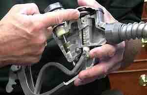 Палец указывает на клапан с мембраной у заправочного пистолета